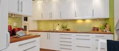 Белая кухня с деревянной столешницей в современном интерьере
